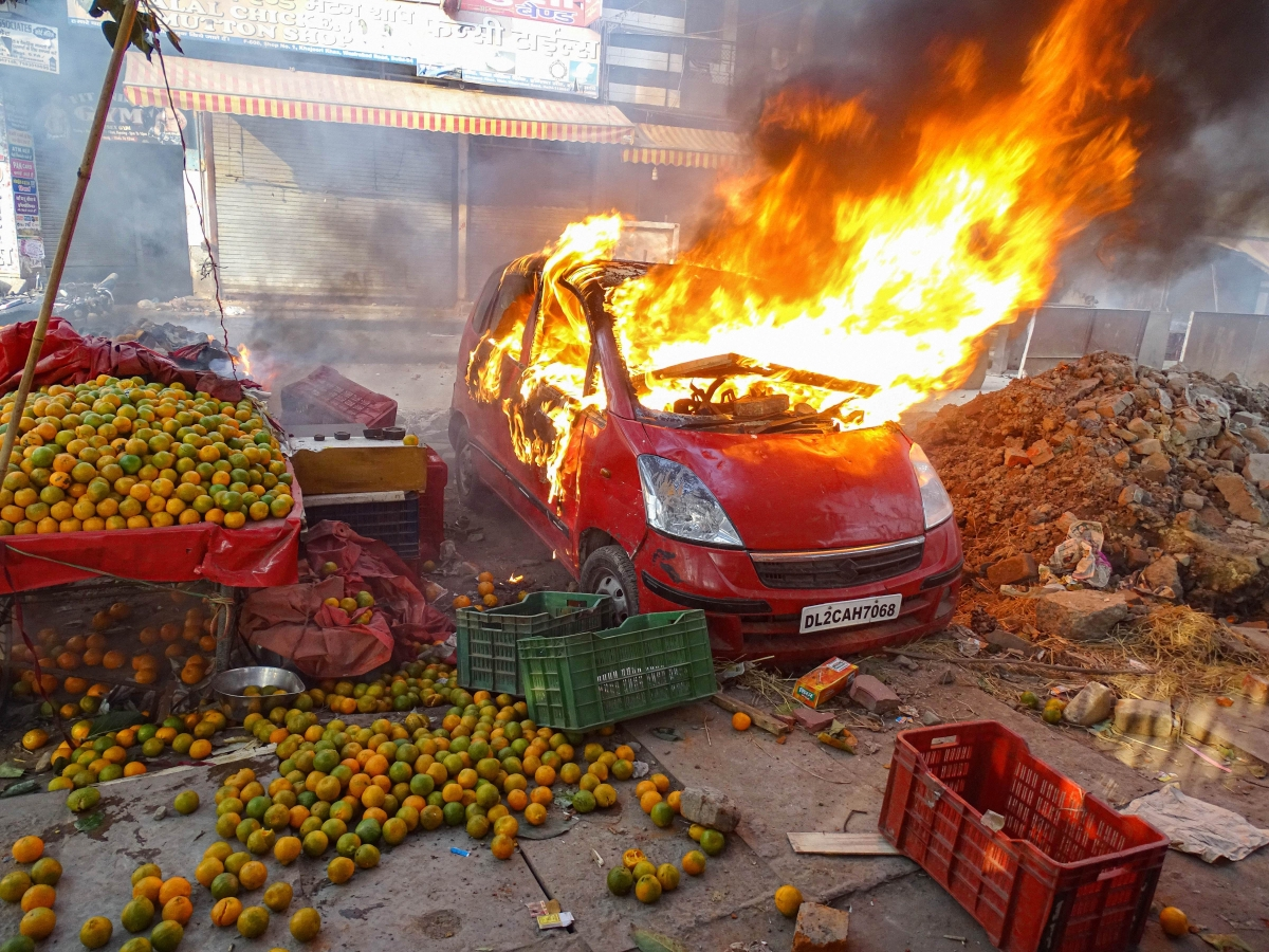 New Delhi: A car in flames near a vandalised fruit shop during clashes between a group of anti-CAA protestors and supporters of the new citizenship act, at Chand Bagh in north-east Delhi,