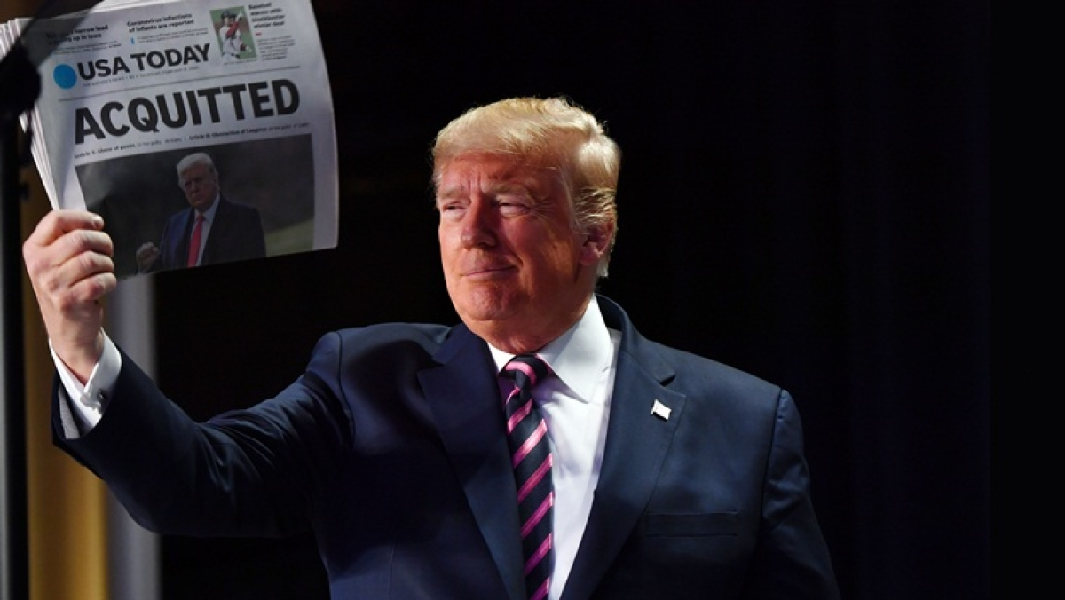 "US President Donald Trump holds up a newspaper that displays a headline ""Acquitted""  as he arrives to speak at the 68th annual National Prayer Breakfast on February 6, 2020 in Washington,DC"