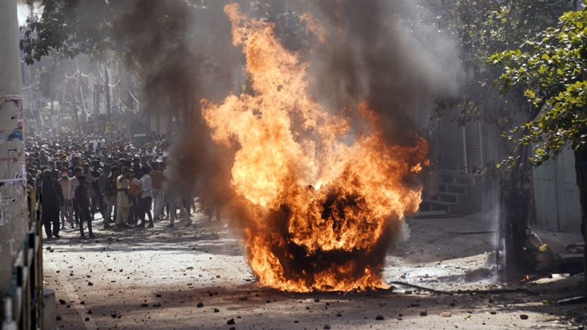 Vehicles set ablaze as protesters throw brick-bats during clashes between anti-CAA protestors and Supporters group of the Citizenship act, at Jafrabad in North-East Delhi on Monday.