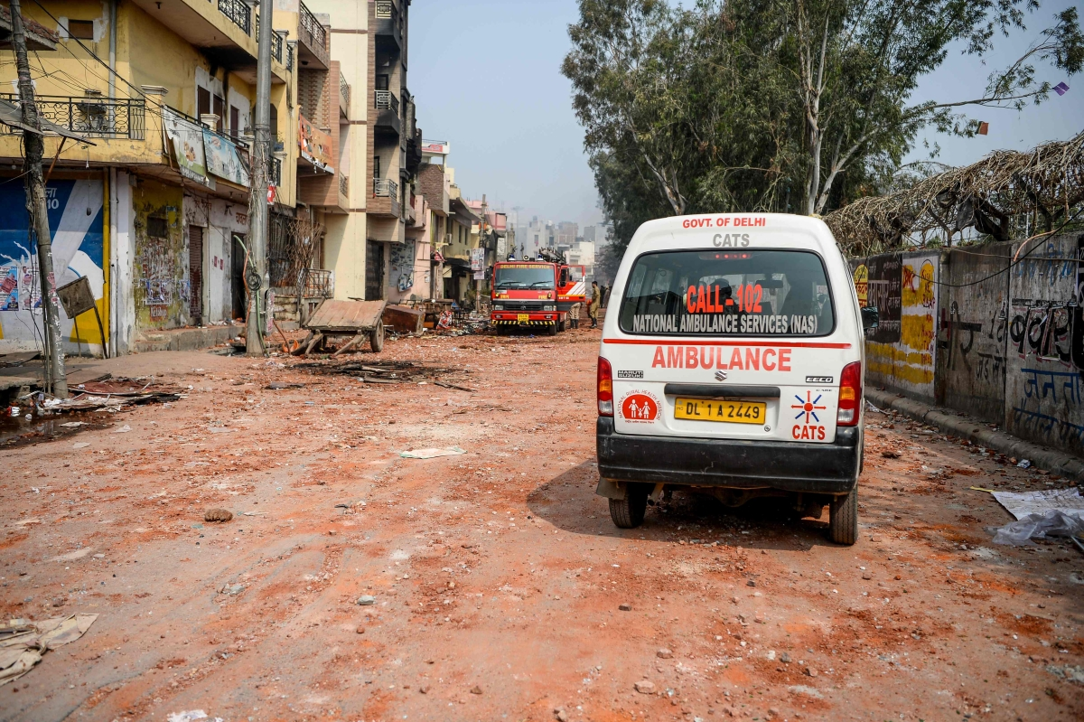 A firefighter vehicle and an ambulance are parked near burnt-out and damaged premises following clashes between people supporting and opposing a contentious amendment to India's citizenship law, in New Delhi on February 26, 2020