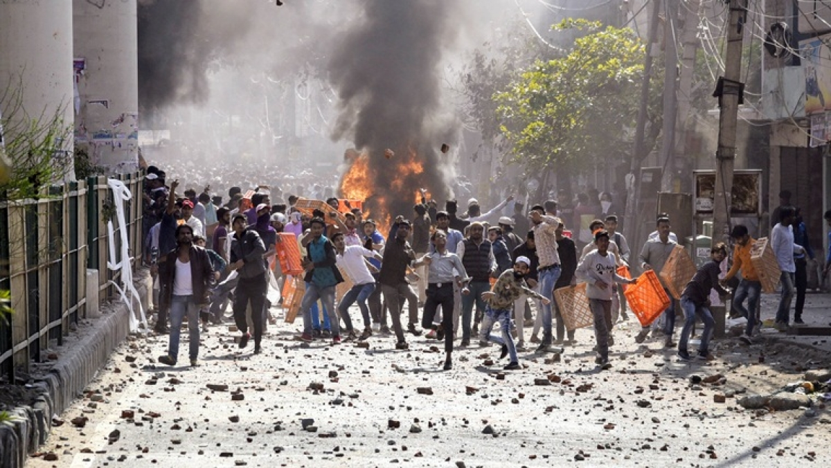 Protestors throw brick-bats during clashes between ani-CAA protestors and the Supporters group of the Citizenship act, at Jafrabad in North-East Delhi on Monday.