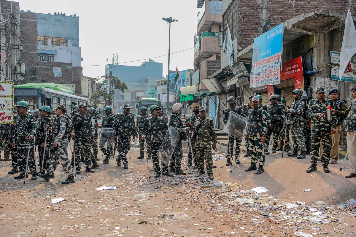 Security personnel stand guard near burnt-out and damaged shops following clashes between people supporting and opposing a contentious amendment to India's citizenship law, in New Delhi on February 26, 2020.