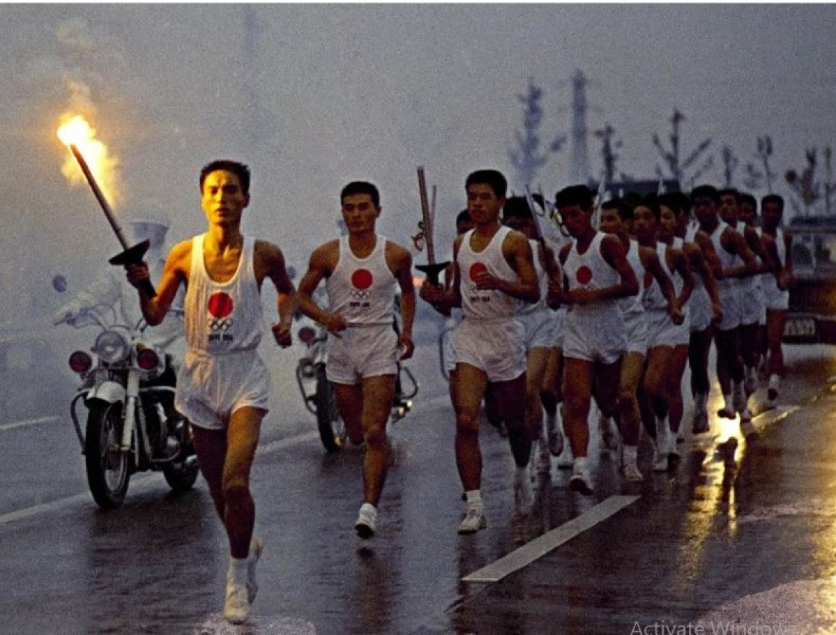 Japanese torchbearers with the 1964 Olympic flame relay team run through the rain on their way to the olympic stadium in OCtober 1964 in Tokyo.