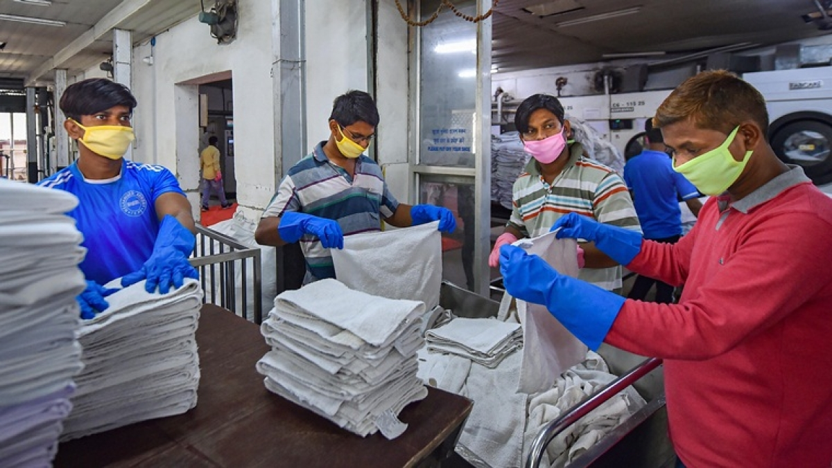 Workers fold washed towels in the wake of deadly coronavirus, at Mechanized Laundry Plant in Kolkata, Monday, March 16, 2020
