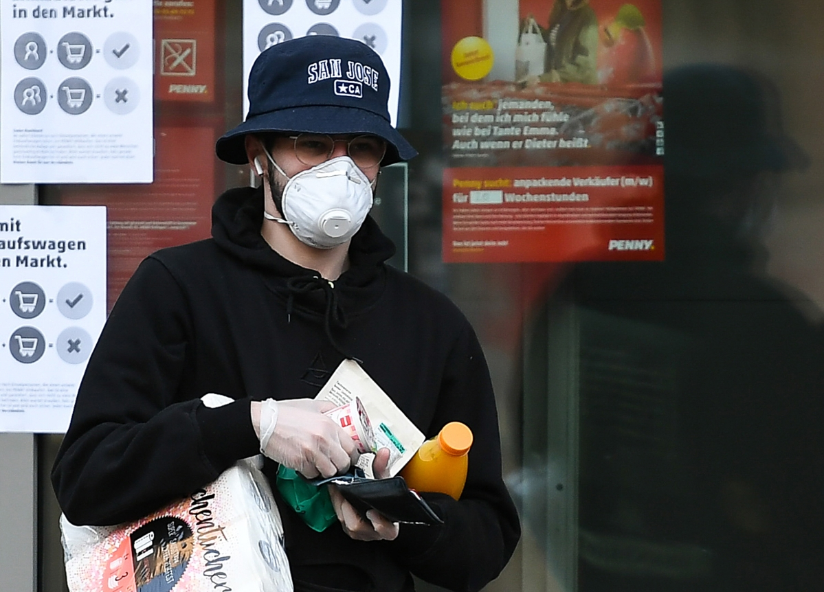 A man wearing a face mask and gloves leaves a supermarket in Frankfurt, Germany, March 25, 2020.