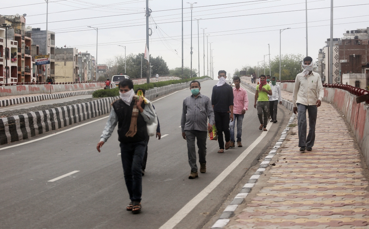 Migrant labourers walk the distance as they leave for their respective villages on the second day of the lockdown announced for the entire country in New Delhi on Thursday.