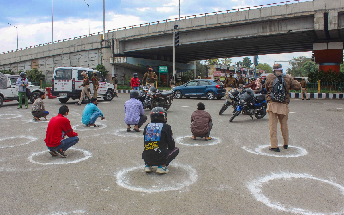 Policemen punish offenders, seated in marked circles to maintain social distancing, who violated the lockdown guidelines by venturing out of their homes unnecessarily during the 21-day complete lockdown to contain the spread of the novel coronavirus, at Vikram Chowk in Jammu, Wednesday, March 25, 2020.