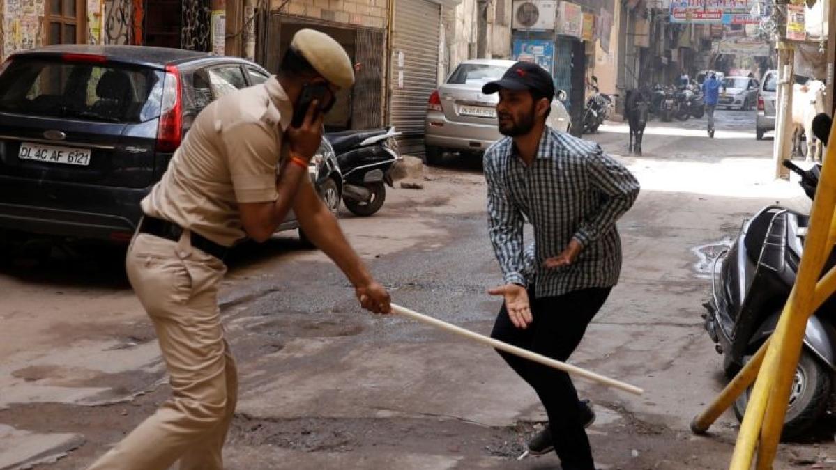 Indian Coppunishing a lockdown violator with stick.