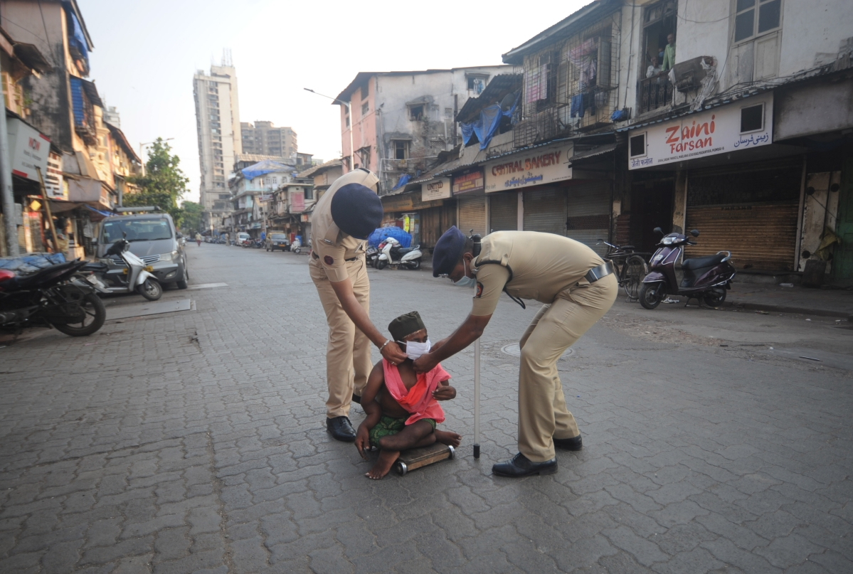 Policemen help a disabled person to wear a mask amid coronavirus pandemic