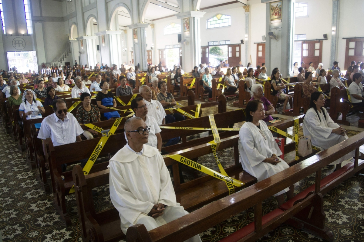 Catholic faithfuls sit on chairs with yellow line tapes, to separate church goers from sitting close to each other, as part of social distancing at a church in Borongan town, Eastern Samar province, central Philippines.