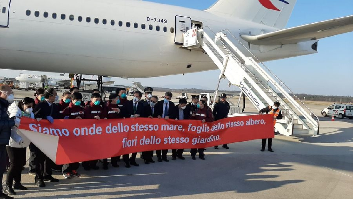 "Members of the second batch of the Chinese medical team along with local people hold a banner reading ""We are waves of the same sea, leaves of the same tree, flowers of the same garden"" and pose for a group photo after they arrived at Milan Malpensa Airport in Milan, Italy, March 18, 2020."