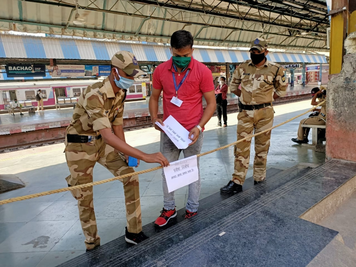 CRPF personnel putting up board for restricting entry in Mumbai railway stations and trains.