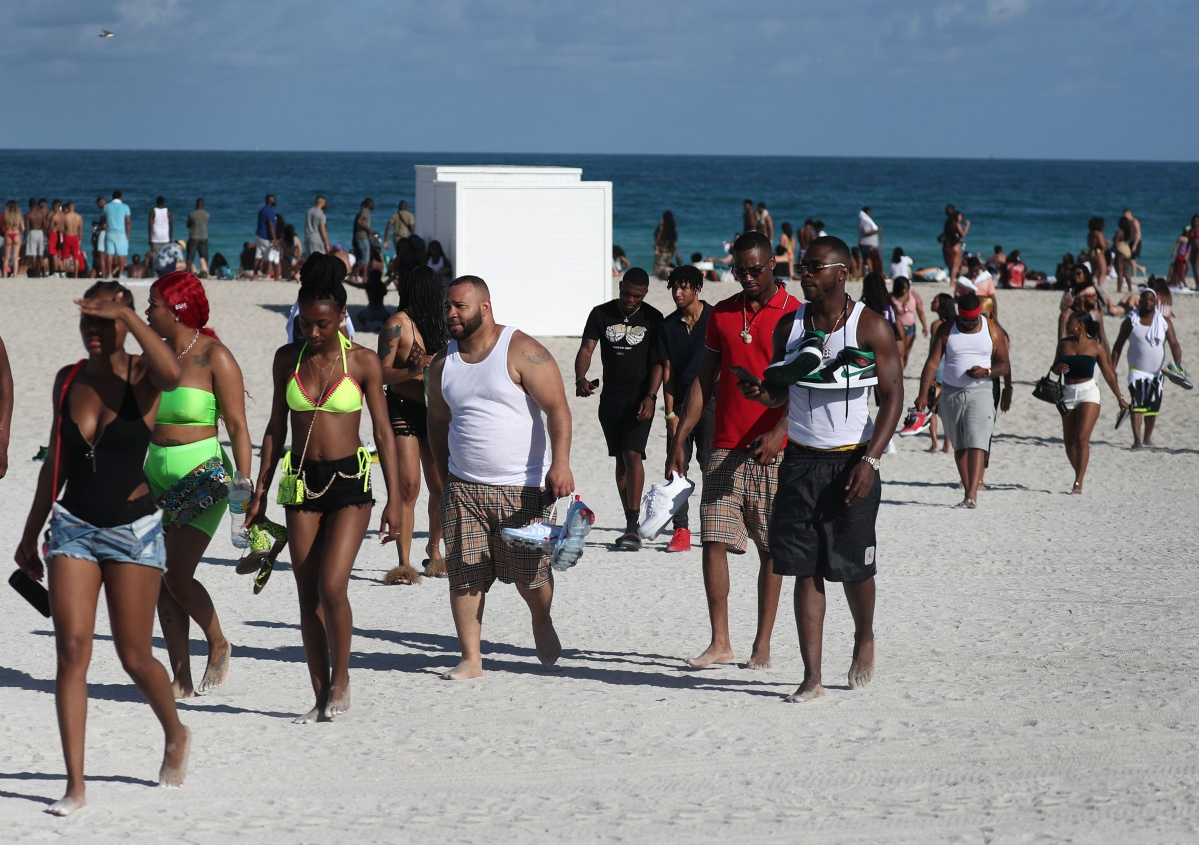 Tourists relax on the beach in Miami Beach, Florida.