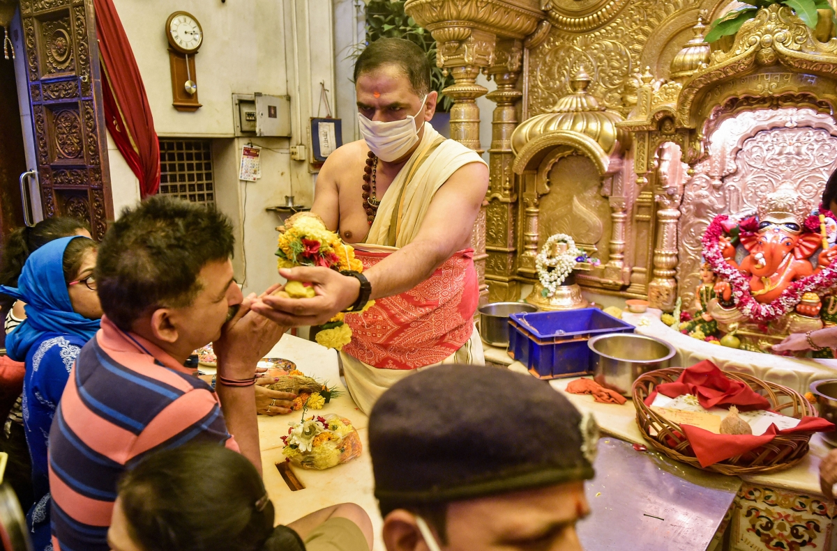priest wearing protective masks as a precautionary measure against the novel coronavirus (COVID-19), offers 'prasad' to a devotee at Siddhivinayak Temple in Mumbai