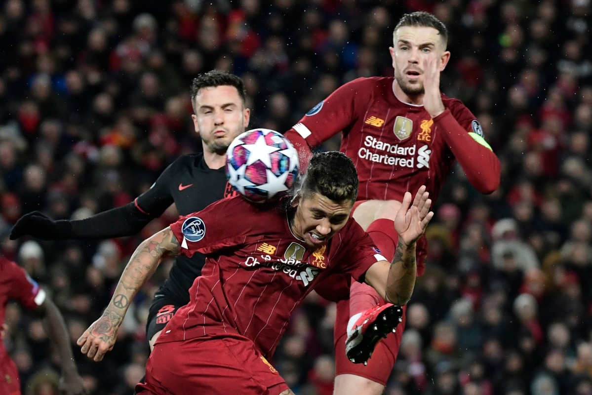 Liverpool's Brazilian midfielder Roberto Firmino (C) controls the ball during the UEFA Champions league Round of 16 second leg football match between Liverpool and Atletico Madrid at Anfield in Liverpool.