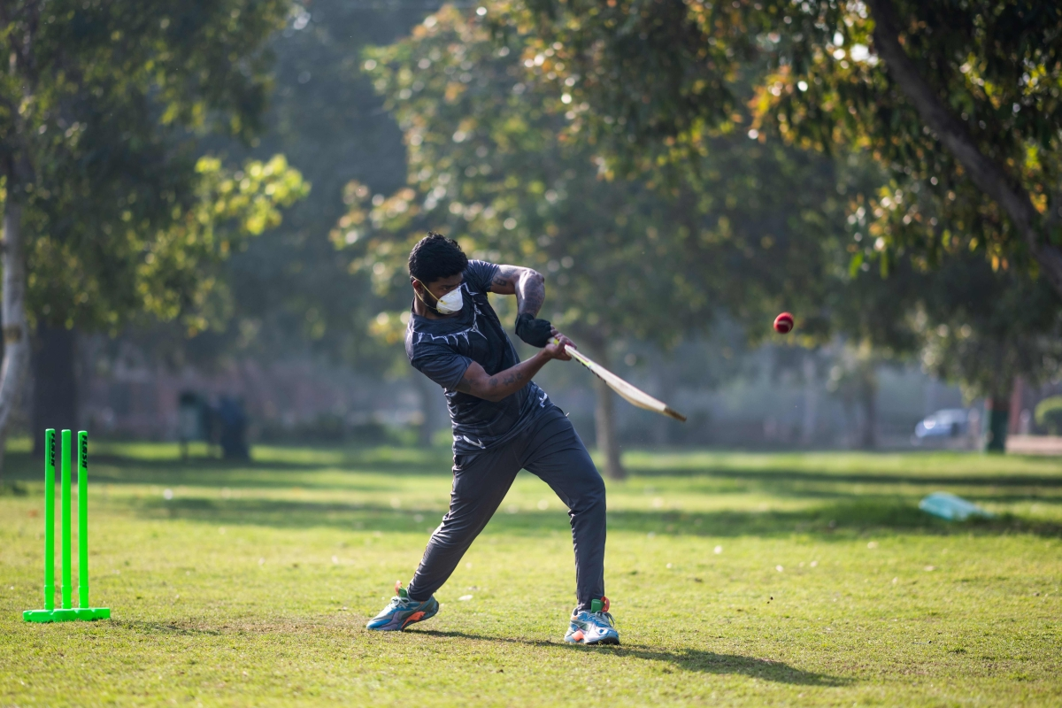 A boy wearing a facemask as a preventive measure against the COVID-19 while he plays cricket with his friends at a park in New Delhi