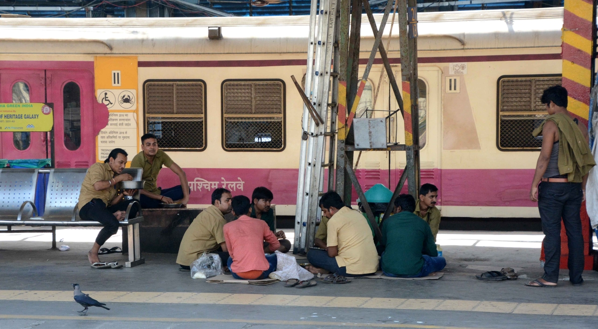 Railway stall workers have lunch on a railway platform during lockdown in Andheri in Mumbai on Monday