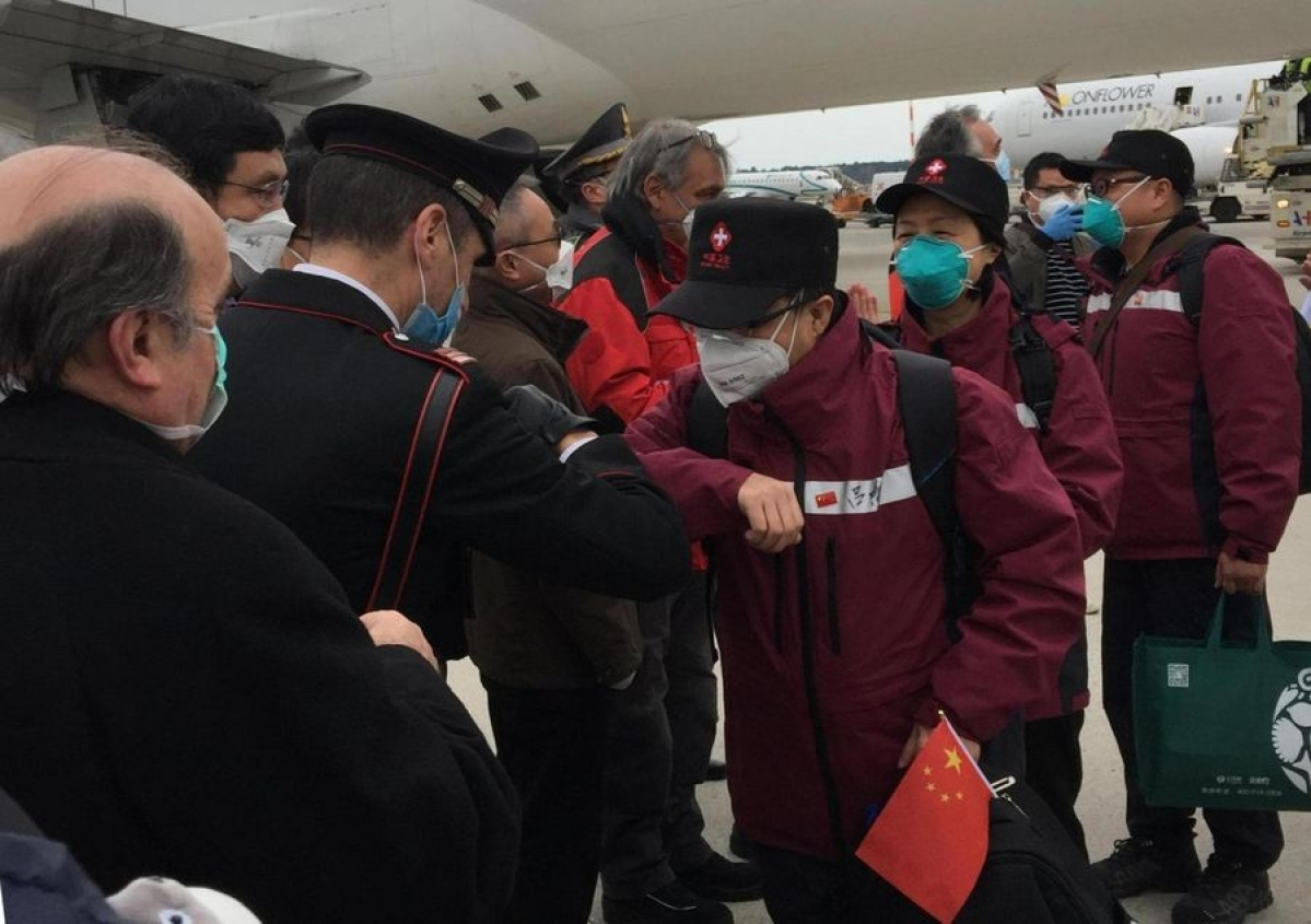 Local people greet members of the third Chinese medical team with an elbow bump instead of handshake as the medics arrive at Milan Malpensa Airport in Milan, Italy, March 25, 2020.