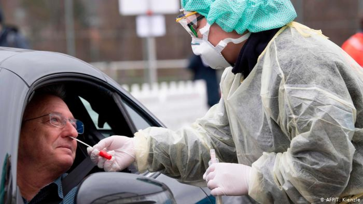 A local district administrator in Germany demonstrates being tested for coronavirus via a drive-through system.