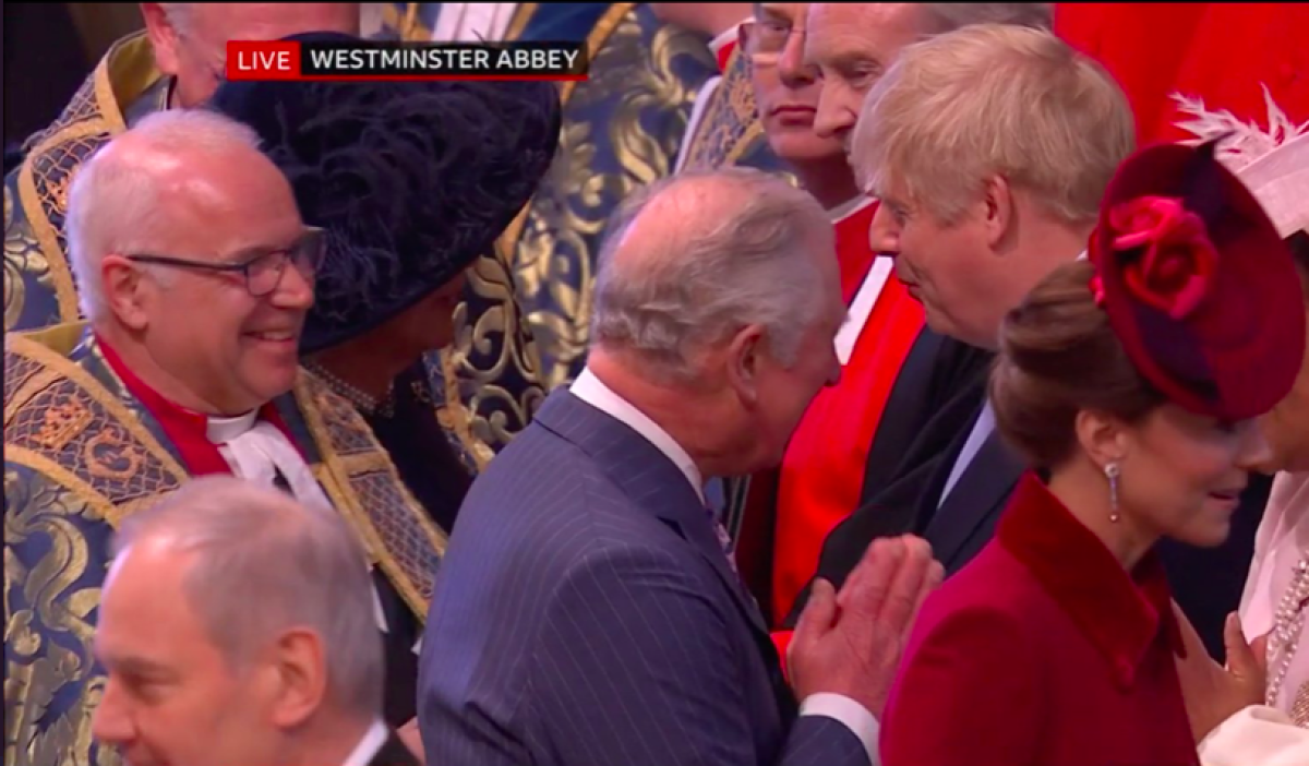 Prince Charles greeting people in the traditional namaste