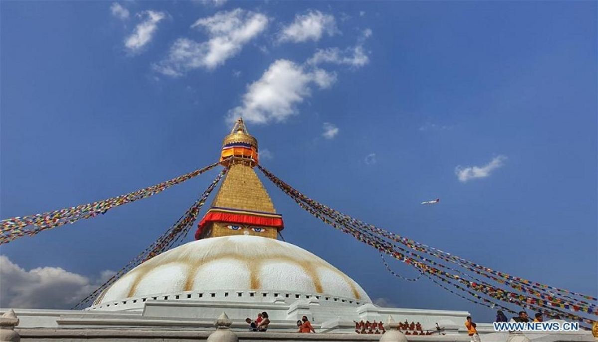 People travel around Boudhanath Stupa, the world heritage site in Kathmandu, capital of Nepal, March 18, 2020. As South Asian countries continue to witness an increase in positive cases, the Nepali government on Wednesday announced measures including restriction of public gatherings to prevent the spread of COVID-19 infection.