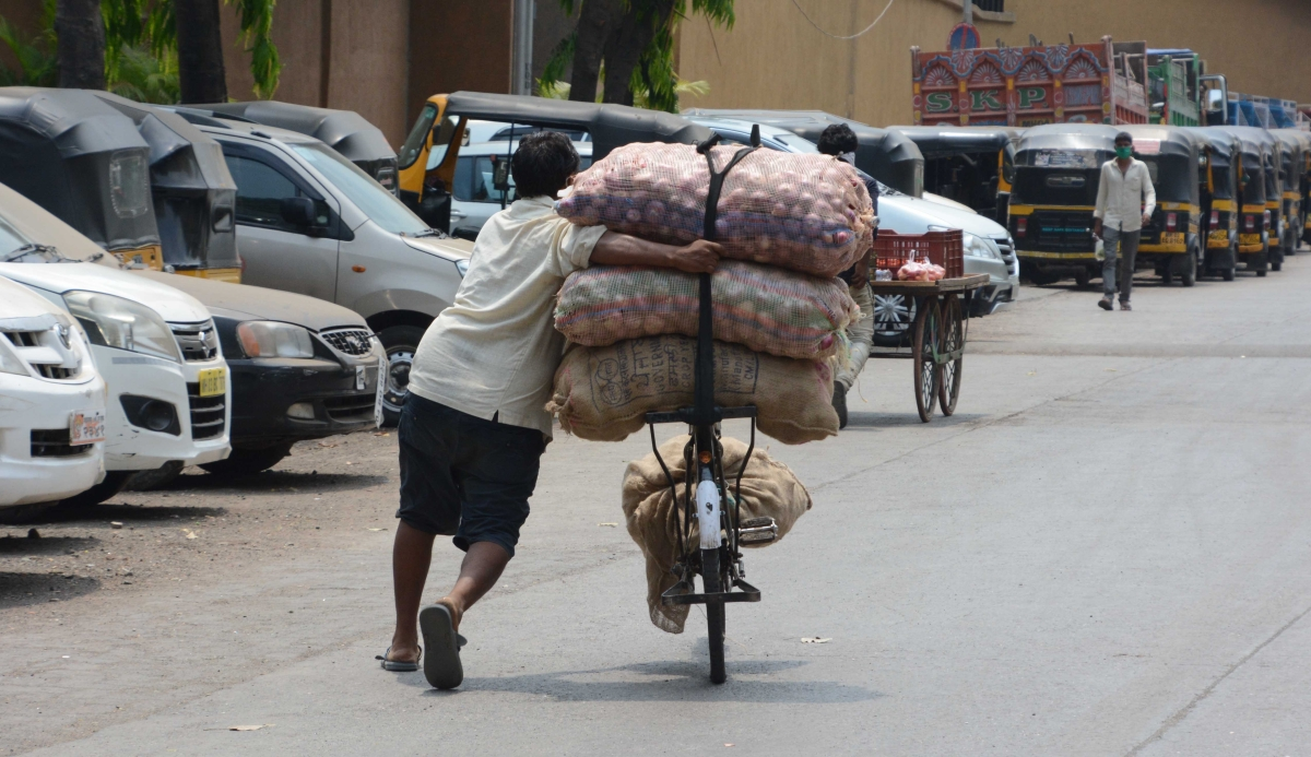A man carrying sacks of vegetables on bicycle.
