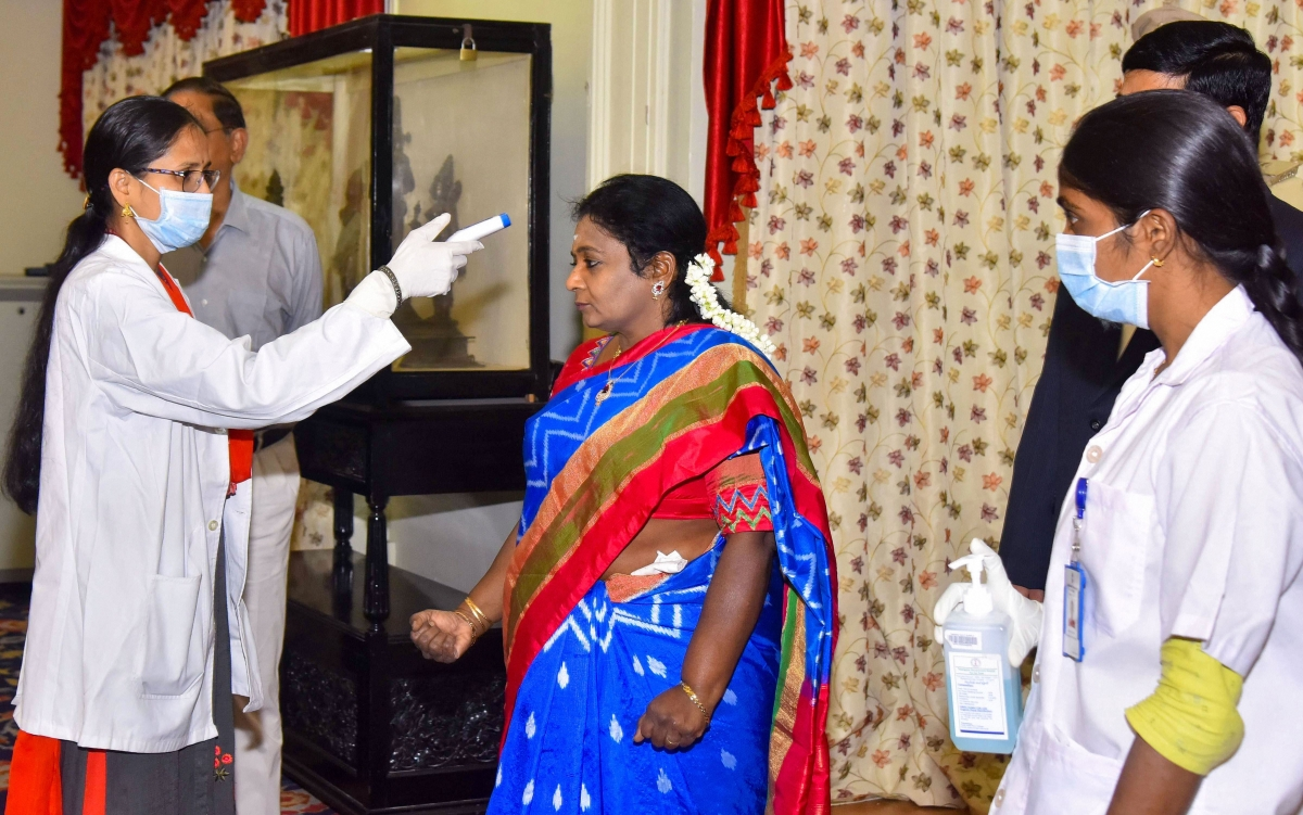 An official uses thermal screening device on Telangana Governor Tamilisai Soundararajan, in the wake of deadly coronavirus, as she arrives at Raj Bhavan, in Hyderabad,  Friday, March 20, 2020.
