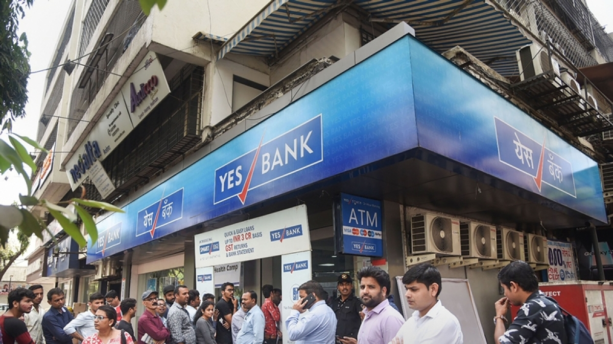 People queuing outside a Yes Bank ATM.