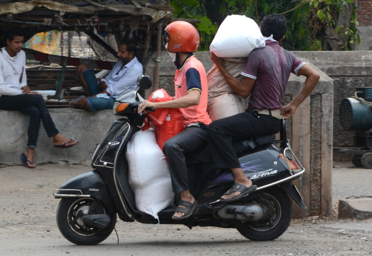 People carrying sacks filled with essential things on two-wheeler.
