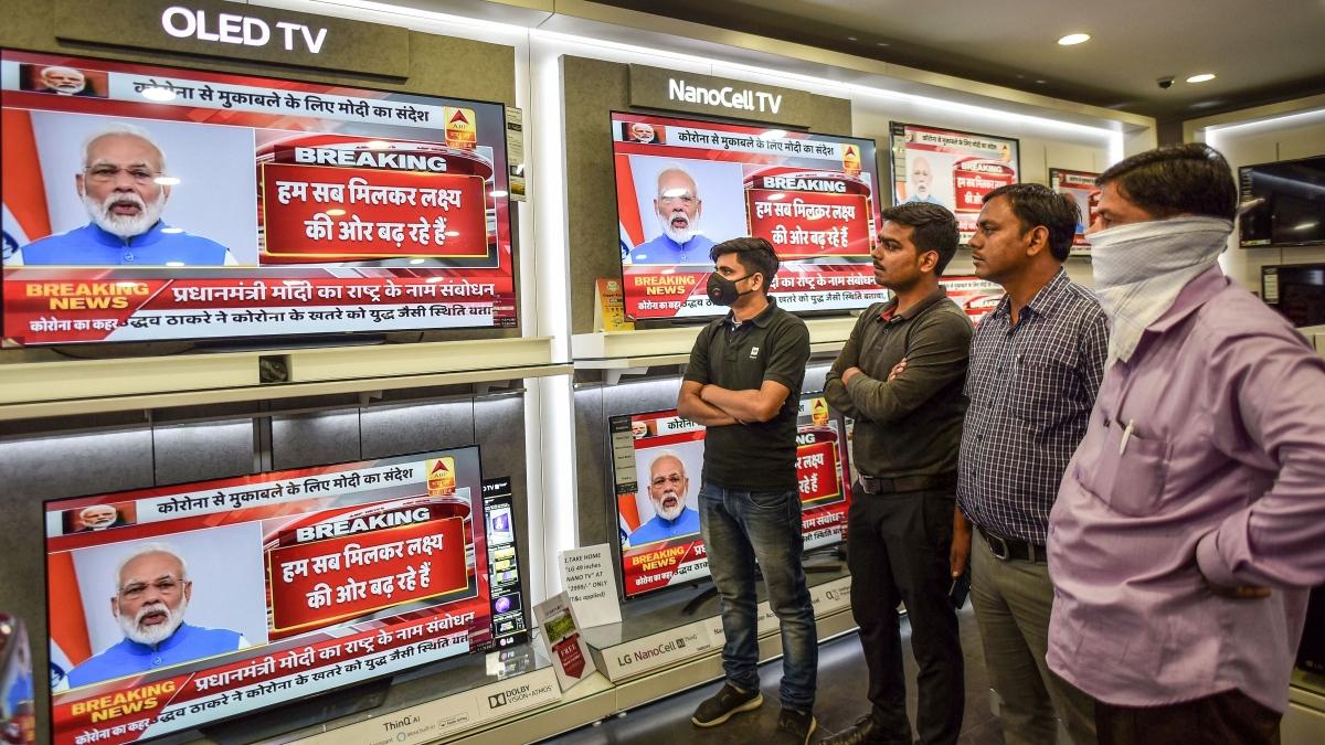 People watch Prime Minister Narendra Modi's address to the nation on coronavirus pandemic in Prayagraj, Thursday, March 19, 2020.