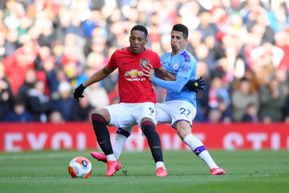 Man United striker Anthony Martial takes the ball from  Man City right-back Jao Cancelo.