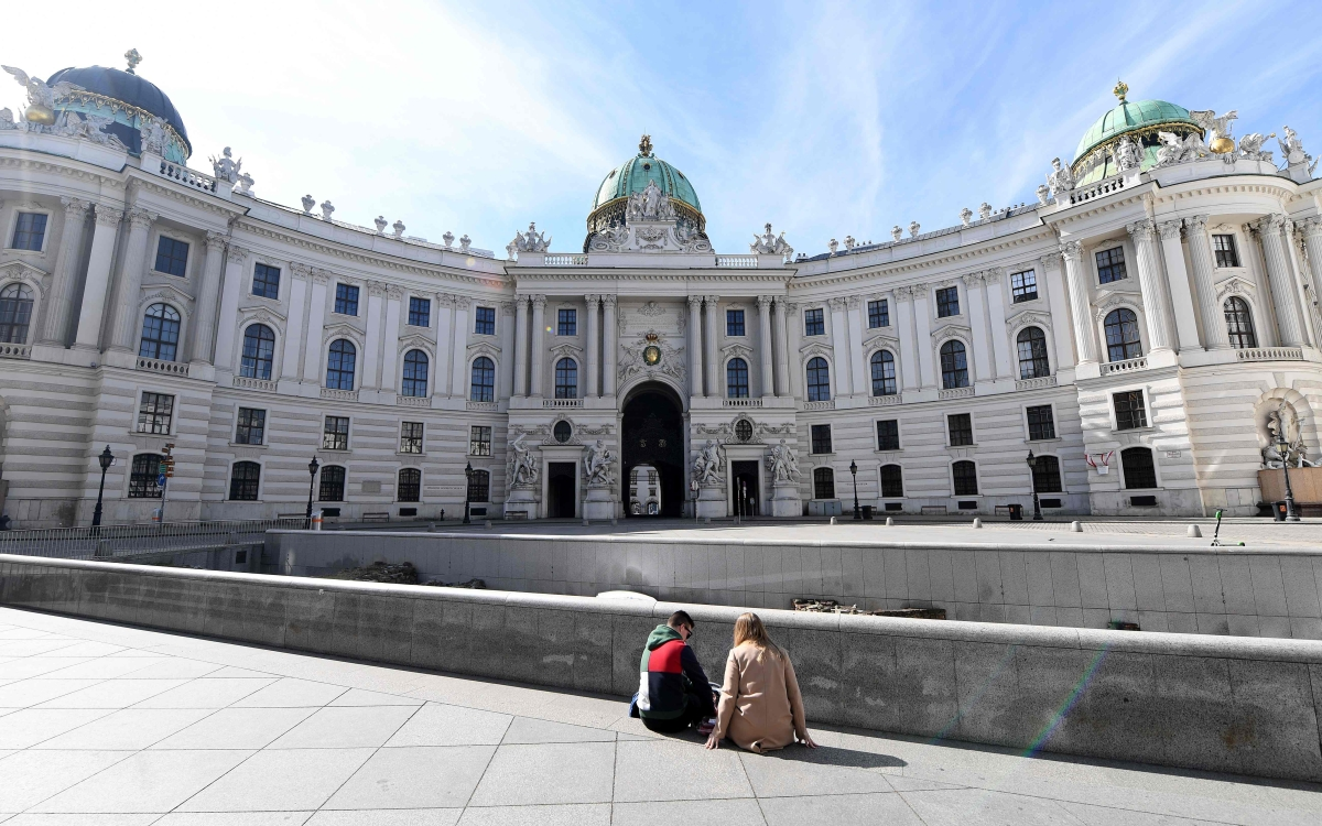 A picture taken which shows  people sitting at an empty square in the center of Vienna, where activities came to a halt due to the novel coronavirus.
