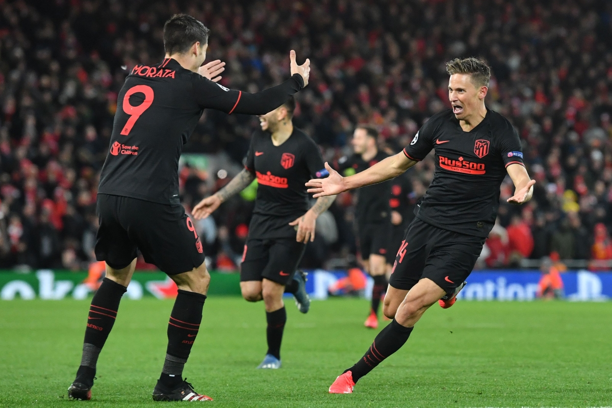 Atletico Madrid's Spanish midfielder Marcos Llorente (R) celebrates scoring his team's second goal during the UEFA Champions league Round of 16 second leg football match between Liverpool and Atletico Madrid at Anfield in Liverpool on Wednesday.