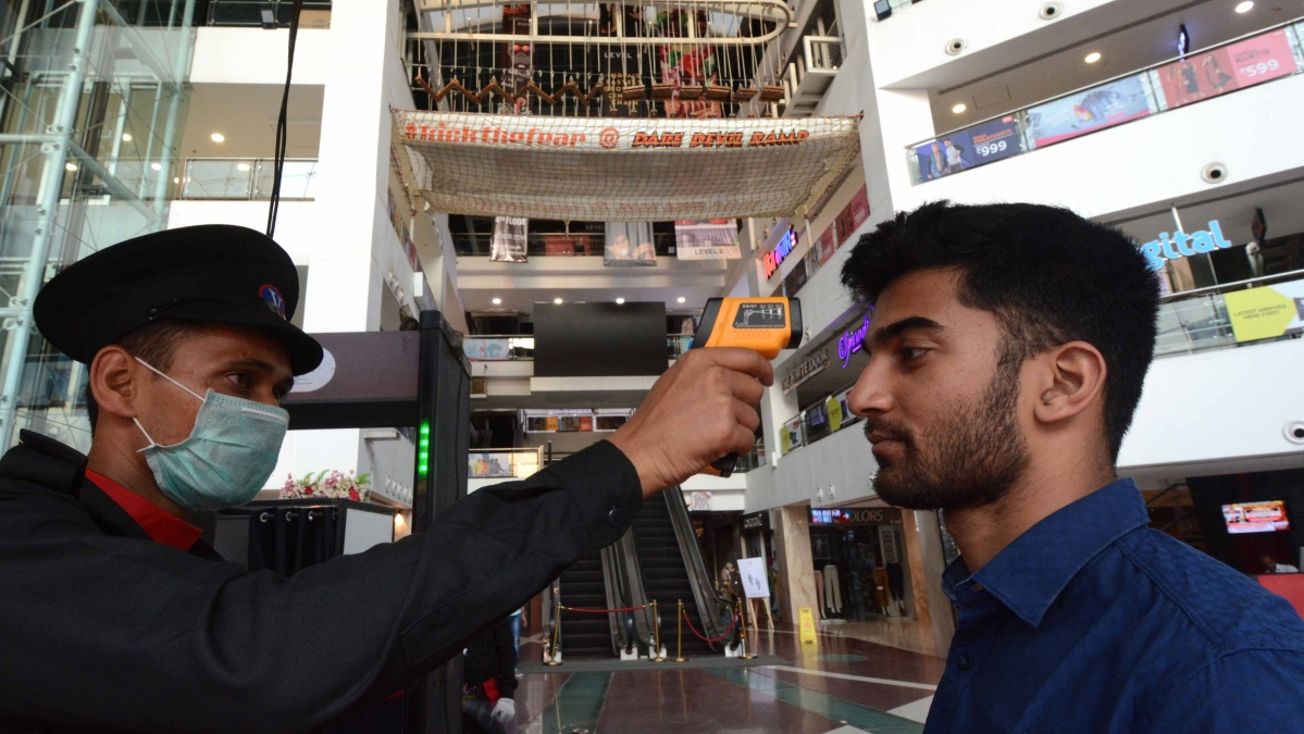 People go through thermal screening amid the coronavirus scare by security official outside at Atria Mall Worli.