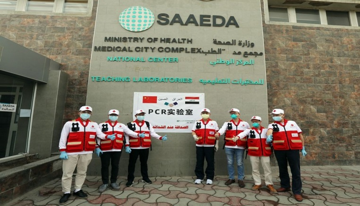 A Chinese team of health experts sent to provide assistance to contain the COVID-19 outbreak in Iraq pose for a group photo outside the new PCR laboratory in Baghdad, Iraq, March 25, 2020.
