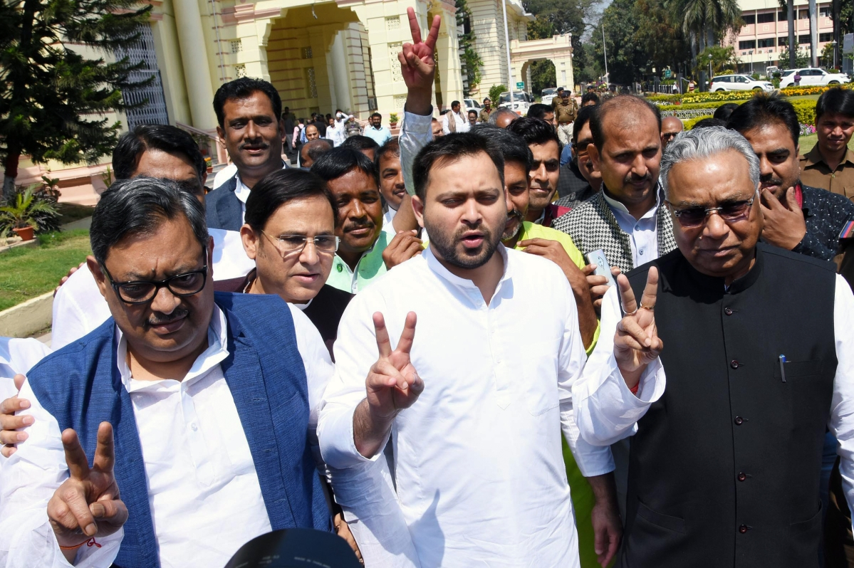 RJD candidate Prem Chandra Gupta (R) with AD Singh (L) and party leader Tejashwi Yadav (C) flash victory sign after filing nomination papers for Rajya Sabha election, in Patna on Thursday.