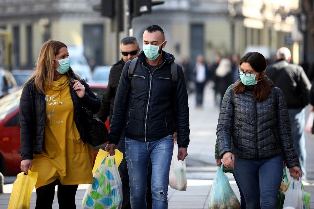 People wearing masks walk on a street in Sarajevo, Bosnia and Herzegovina (BiH) on March 18, 2020.