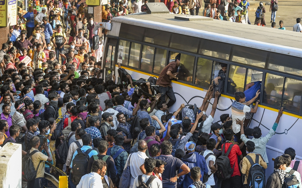 Passengers rush to board State Express Transport Corporation of Tamilnadu (SETC) bus after lockdown announcement in view of coronavirus pandemic, at Koyambedu bus terminal, in Chennai, Monday, March 23, 2020.