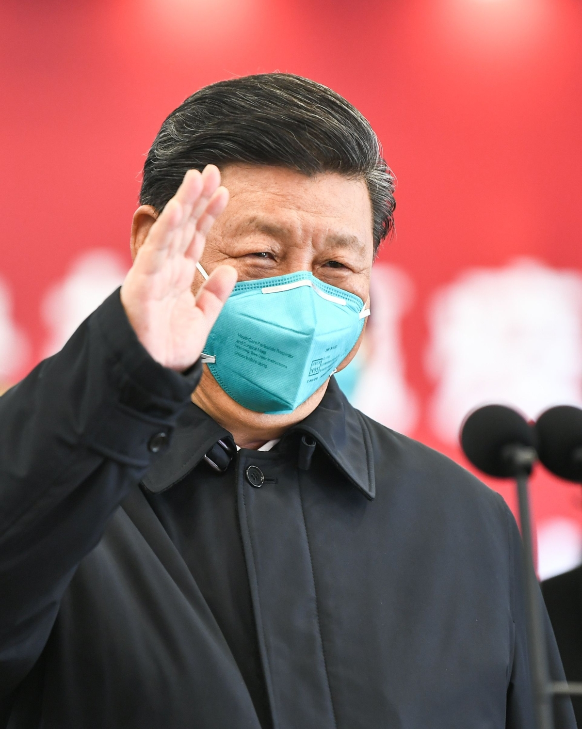 Xi Jinping waves to a coronavirus patient and medical staff via a video link at the Huoshenshan hospital in Wuhan on March 10, 2020