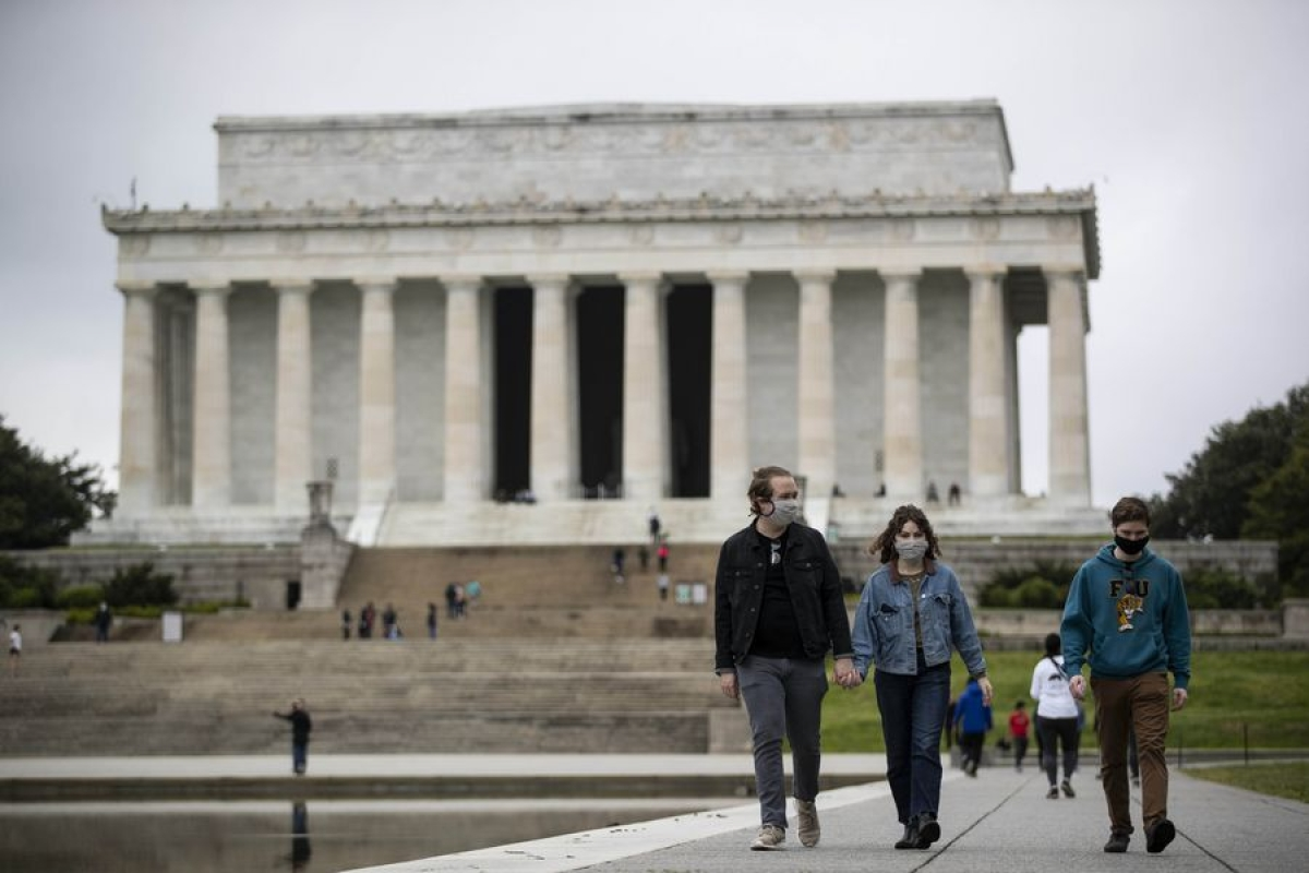 People wearing masks walk near the Lincoln Memorial in Washington D.C., the United States, on April 26, 2020.