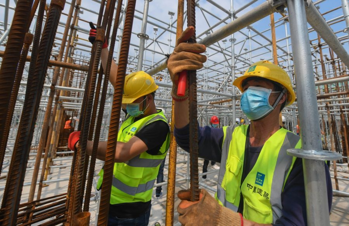 Staff members work at a construction site in Wuhan, central China's Hubei Province, March 26, 2020.