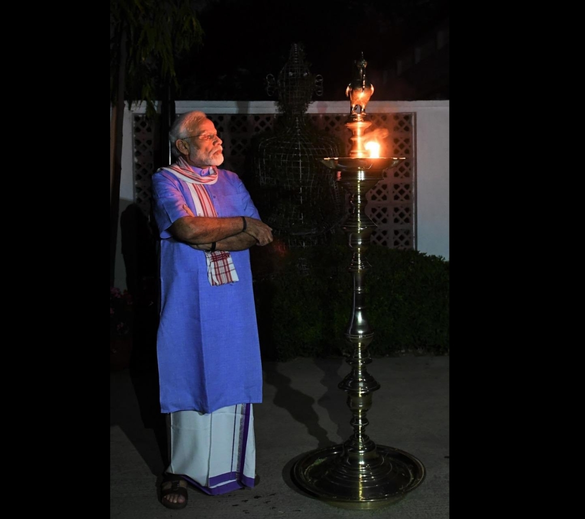 Lord of Light? PM Modi's strikes a pose as he lights a lamp in darkness - see pics