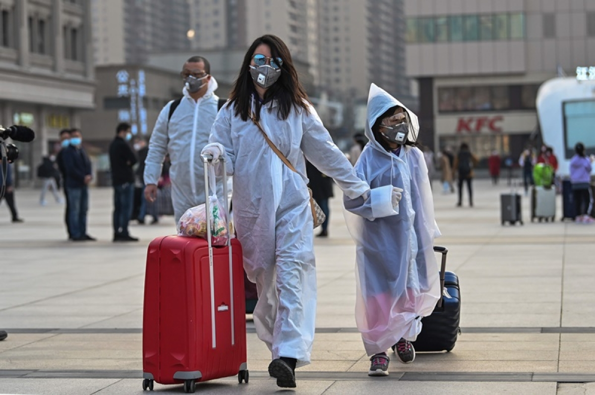 People wearing protective clothing and masks arrive at Hankou Railway Station in Wuhan, to board one of the first trains leaving the city in China