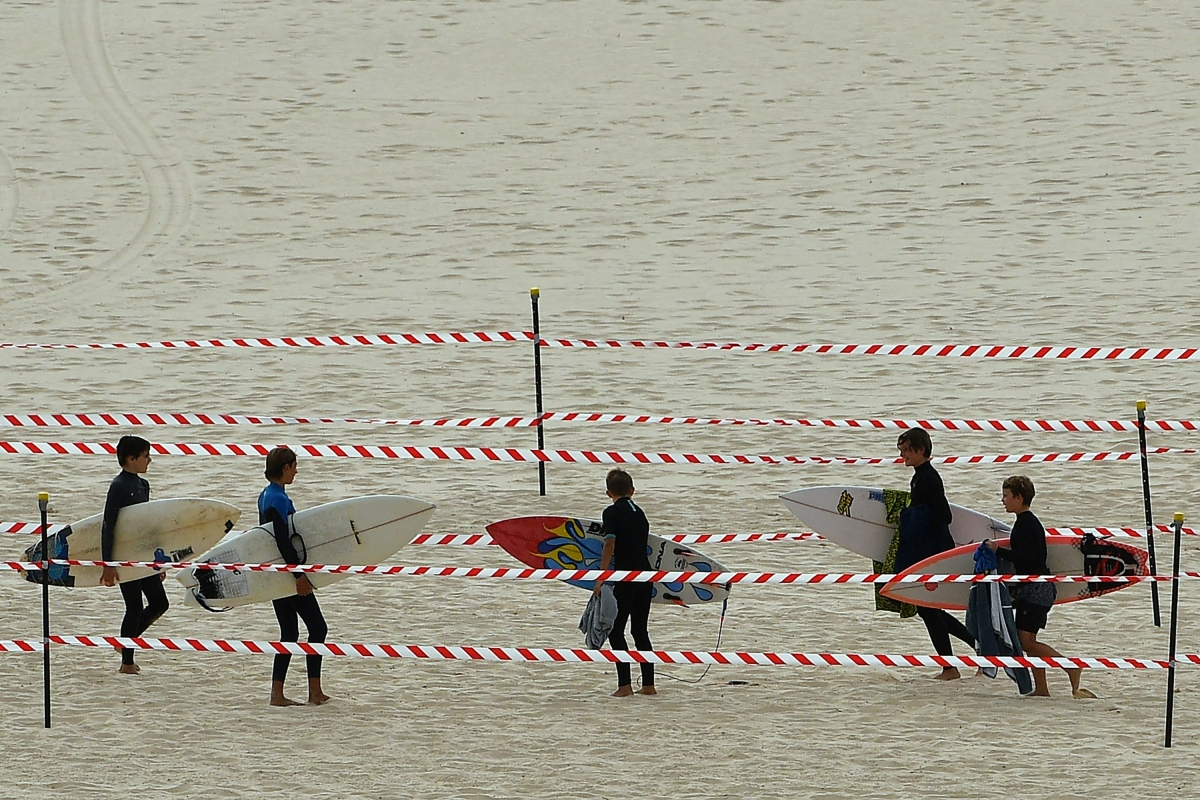 Surfers carry their boards on Bondi Beach after it reopened following a five week closure in Sydney on April 28, 2020.