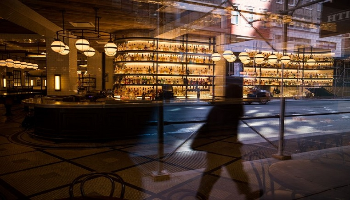 A pedestrian is reflected in a window of a closed dining room and bar of The Smith in New York, the United States, March 26, 2020.