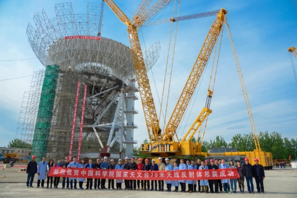 Scientists and workers pose for a photo after the antenna installation at the construction site of the steerable radio telescope in Wuqing District of northern China's Tianjin.