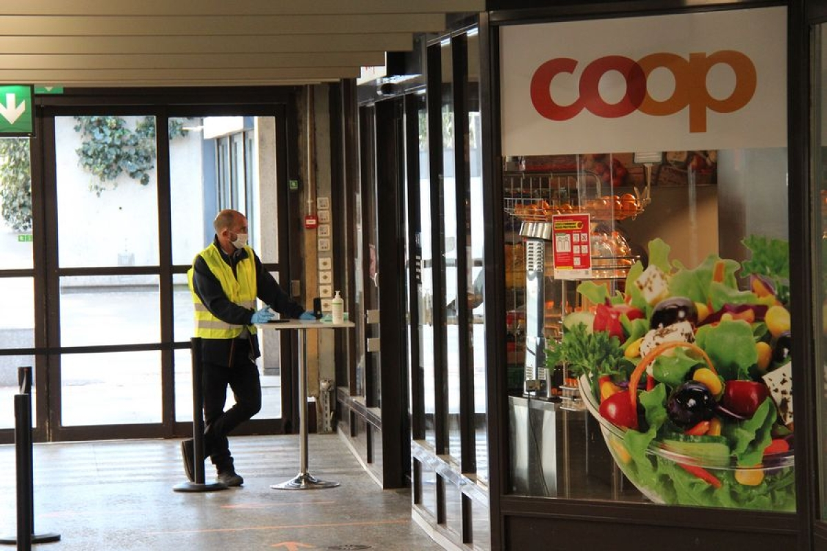 A man wearing a face mask works at the entrance of a supermarket in Geneva, Switzerland, on March 31, 2020.
