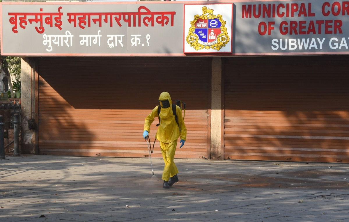 A BMC worker spraying disinfectant area in front of canon pavbhaji center, at CSMT in Mumbai.