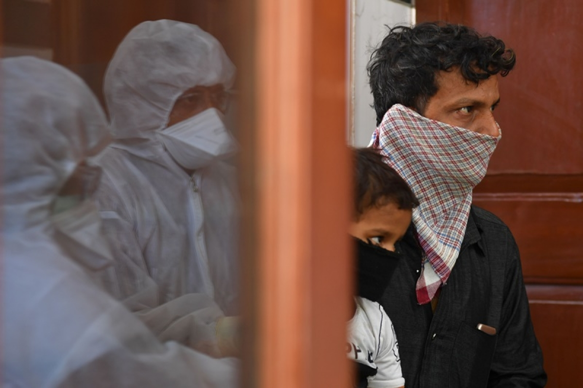 Doctors are reflected in a window pane as they take down details of a man and his child at a municipal health centre before being tested for the COVID-19