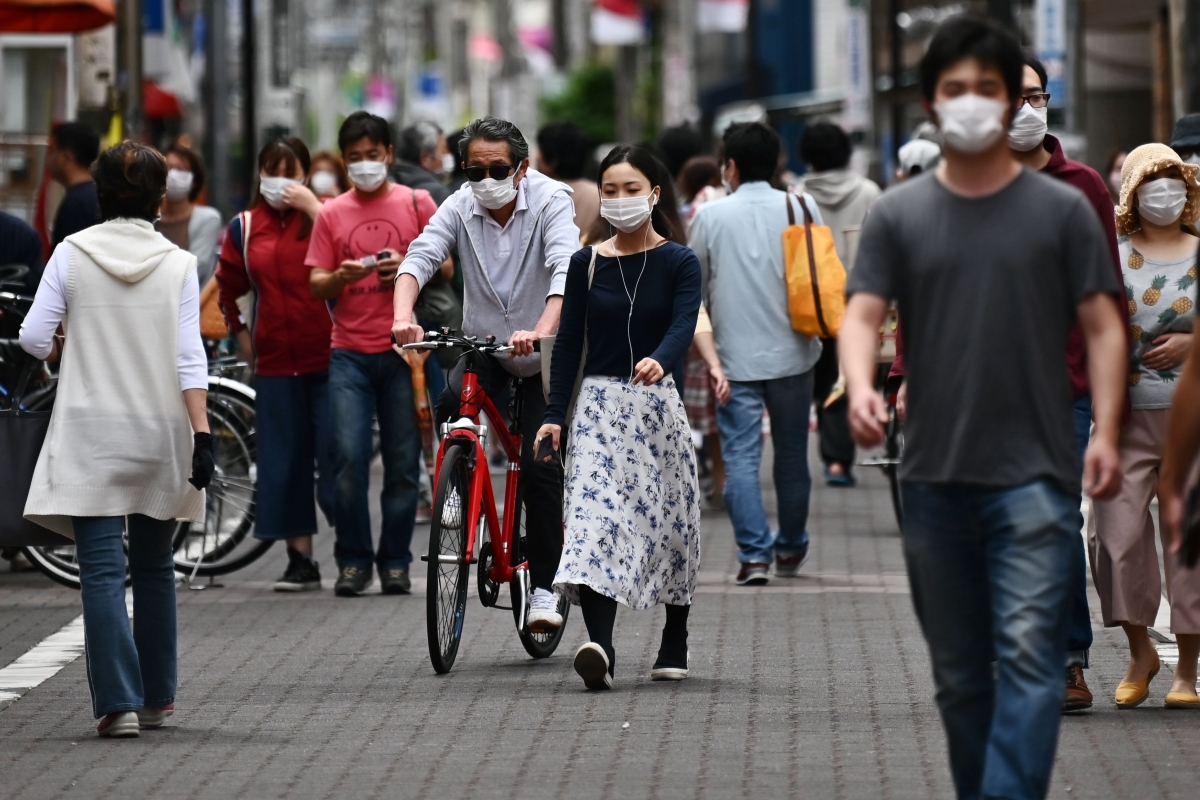 People wearing face masks walk on the streets of Tokyo.